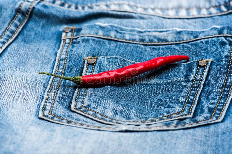 Pepper on back pocket of blue jeans. Pocket of jeans with red chilly pepper, denim background. Hot sensations concept. Piquant secret in pocket of pants, top stock photography