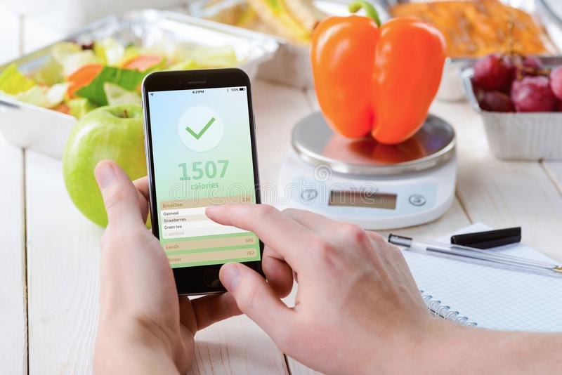Pepper and calorie counter app. Smartphone with a calorie counter app, close-up. Paper notebook, a food scale, a pepper, an apple, salad, grapes and a pie on the stock images