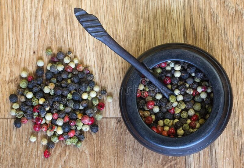 Pepper corns in a wooden pot. stock images