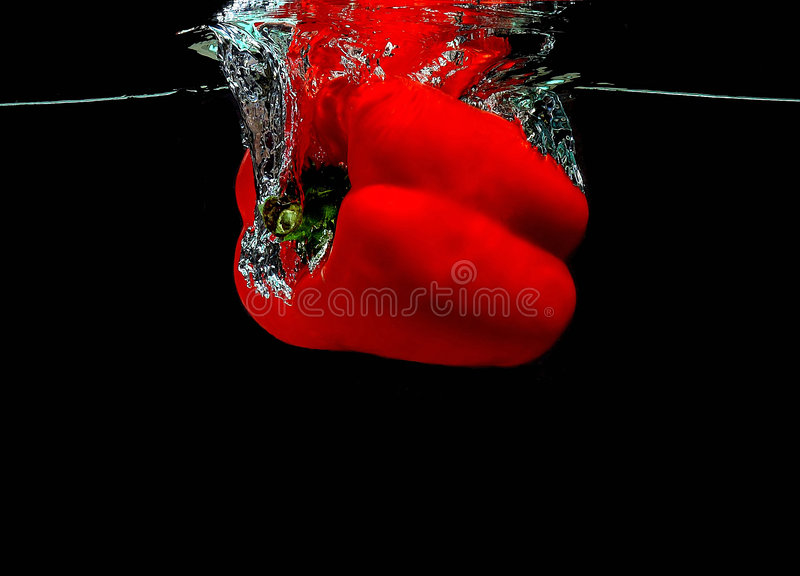Pepper falling into water stock images