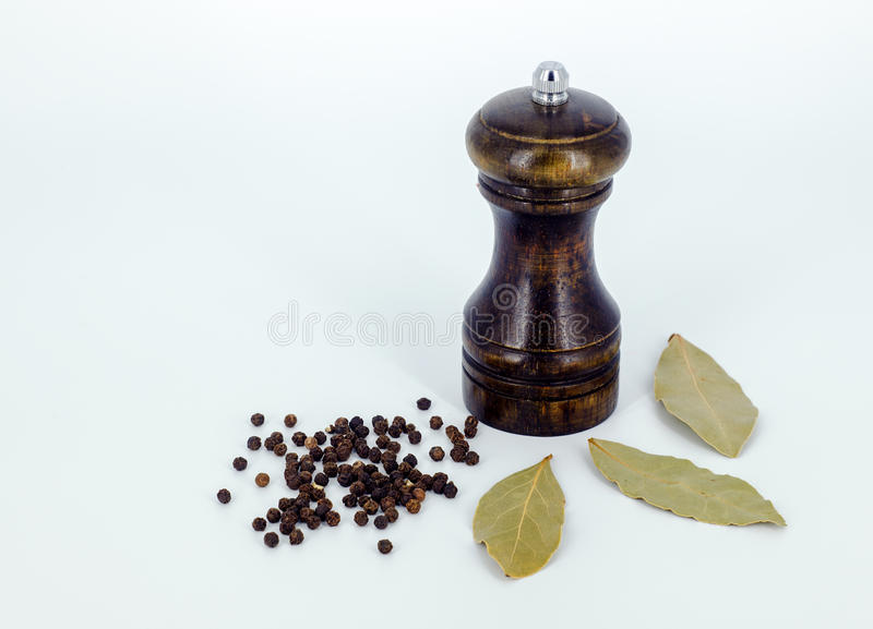 A pepper mill with black pepper corns in white background. royalty free stock photography
