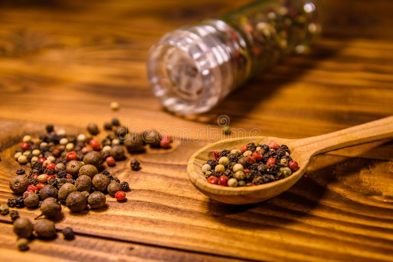Pepper mill and scattered spices on the wooden table royalty free stock images