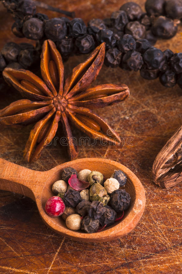 Pepper mix with star anis. Pepper mix in wooden spoon with star anis and on wooden background stock photography