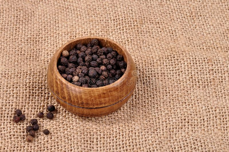 pepper not ground in a wooden bowl on a ragged background. royalty free stock image