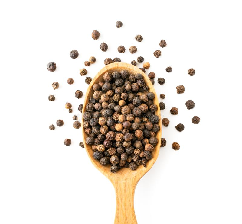 Pepper peas in a wooden spoon on a white. The view of the top. royalty free stock photo