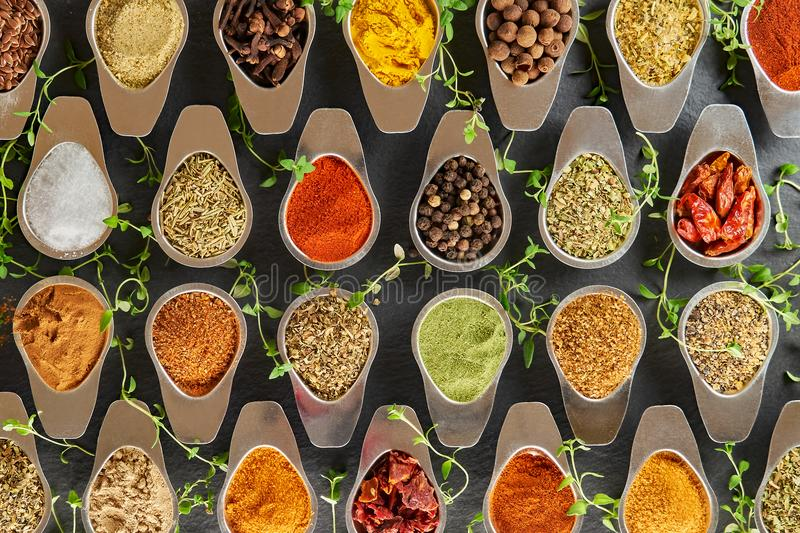 Various spices for dishes on a black background, camera from above stock photos