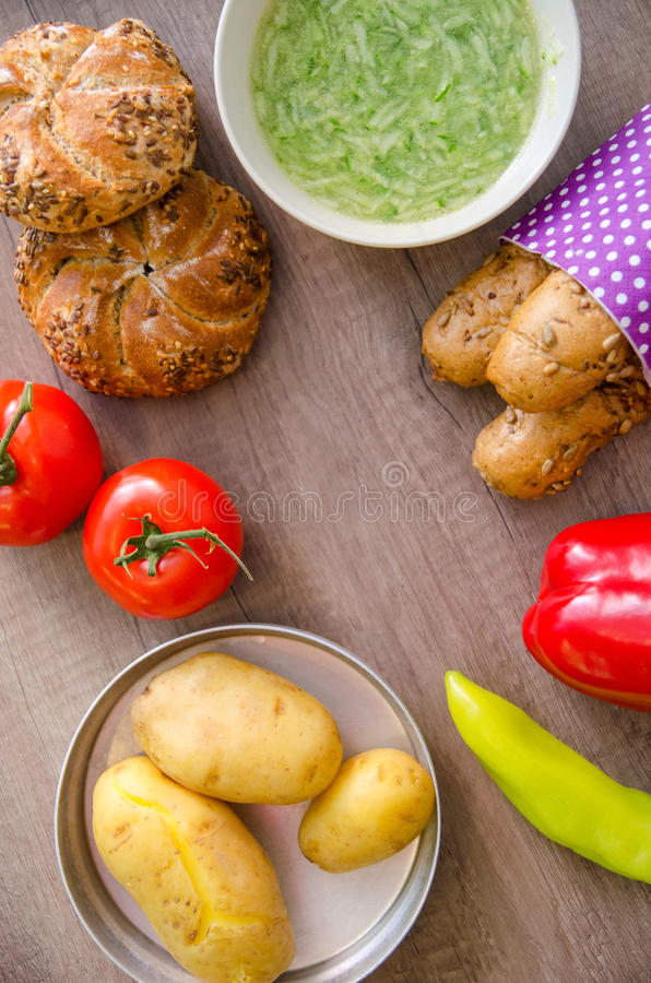 Pepper, potato, kaiser bun and baguette on wood table. Vegetarian bio food concept. Pepper, potato, kaiser bun and baguette on wood table. Vegetarian bio food stock photo