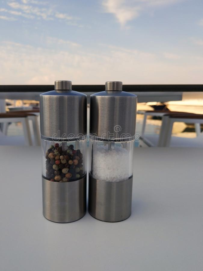 Pepper and salt mills on a restaurant table royalty free stock photo