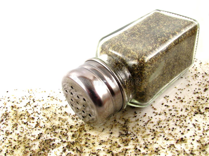 Pepper Shaker. Glass pepper shaker with spilled ground black pepper on a white background royalty free stock photos