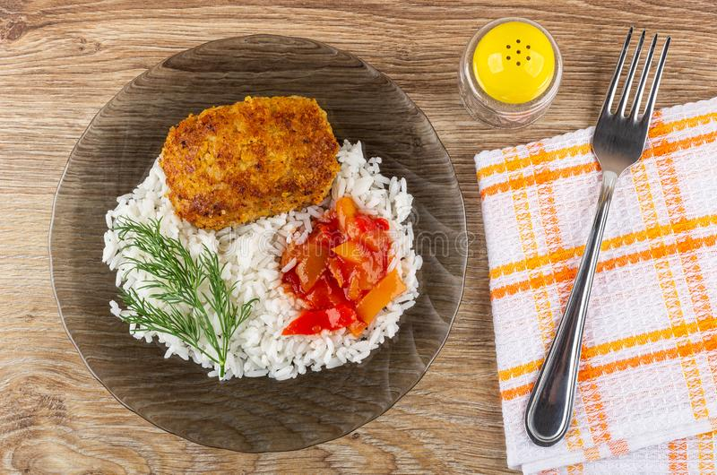 Pepper shaker, plate with fried patty, rice, lecho, dill, fork on napkin on table. Top view. Pepper shaker, transparent brown plate with fried patty, rice, lecho royalty free stock images