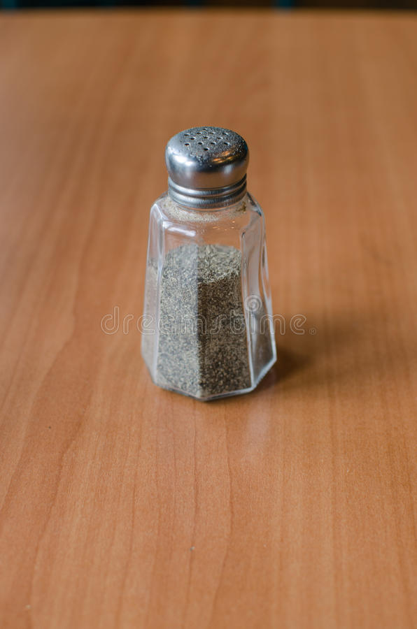 Pepper shaker on wooden table royalty free stock photography