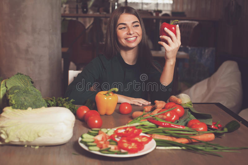 Pepper and smilling woman. Woman with red pepper is sitting at the table with lots of vegetables stock photo