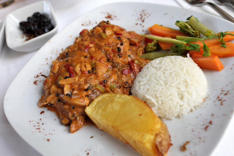 Pepper steak with rice and slice of potato stock photography