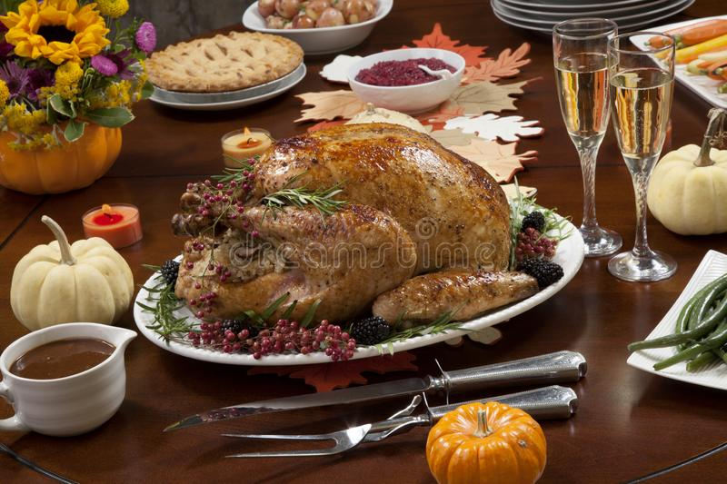 Pepper Turkey for Thanksgiving. Roasted pepper turkey for Thanksgiving, garnished with pink pepper, blackberry, and fresh rosemary twigs on a dinner table royalty free stock image