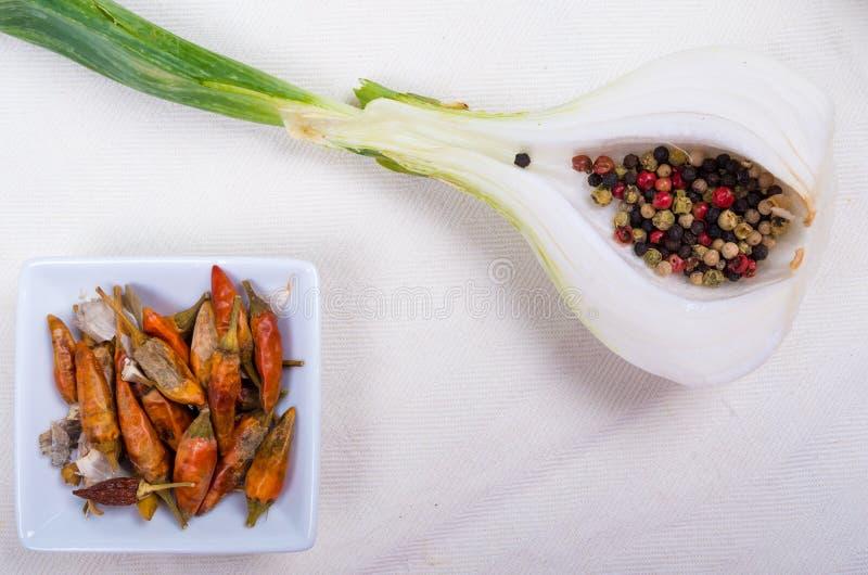 Peppercorns των διάφορων χρωμάτων περιείχαν σε μισό κρεμμύδι και ένα W στοκ εικόνες