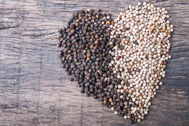 Peppercorns in shape of heart. Black and white peppercorns in shape of heart on wooden table top stock photo