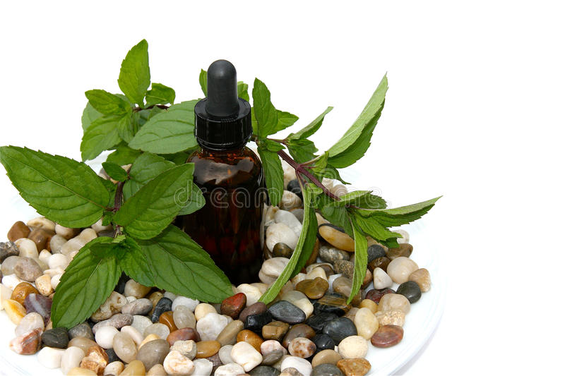 Peppermint Aromatherapy. Aromatherapy concept with fresh peppermint leaves and a bottle of essential oil on a plate of gems and pebbles isolated on a white royalty free stock photo