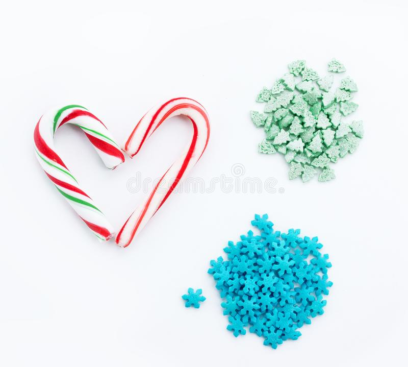 Peppermint candy cane, Christmas tree green sugar sprinkles, blue snowflake sugar sprinkles for decoration festive sweet food royalty free stock photos