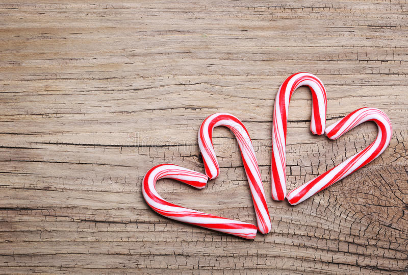 Peppermint Candy Canes in Heart Shapes on wooden background royalty free stock photo
