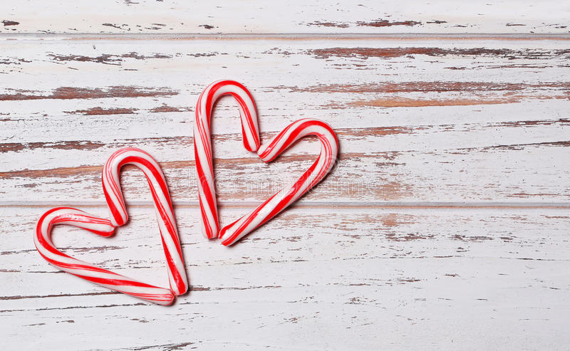 Peppermint Candy Canes in Heart Shapes on wooden background royalty free stock images