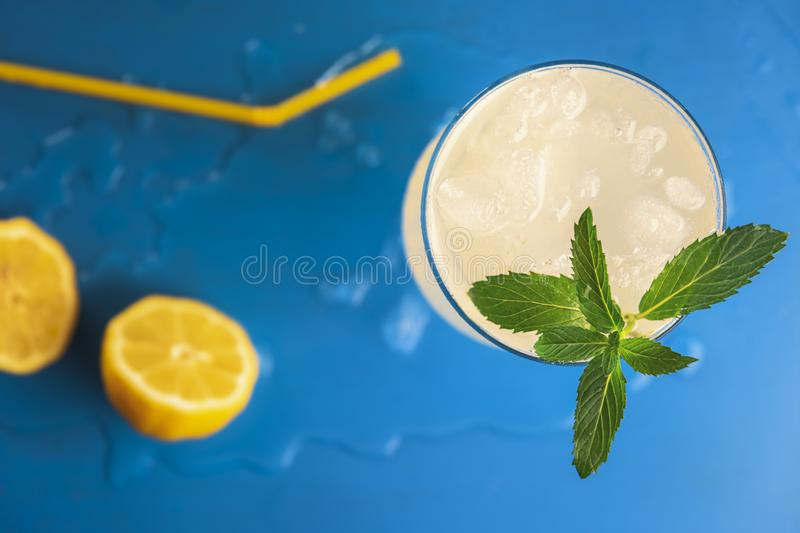 Peppermint leaves in lemonade glass on blue table stock photos