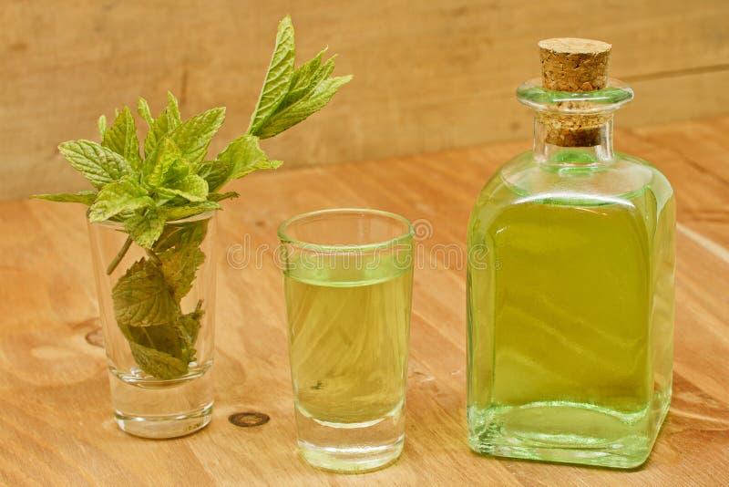 Peppermint plant, liqueur bottle and shot stock images