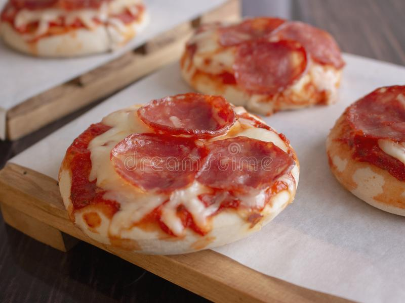 Pepperoni and Mozzarella Cheese Mini Pizzas served on Wooden Plates over White Food Paper. Delicious Pepperoni and Mozzarella Cheese Mini Pizzas served on Wooden royalty free stock photo