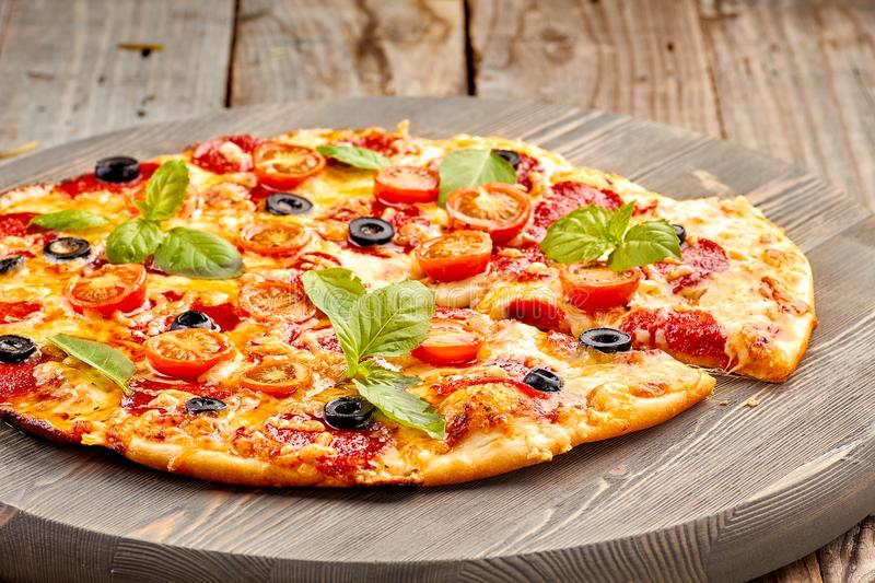 Pepperoni pizza with basil leaves and cherries tomatoes on wooden table royalty free stock photos