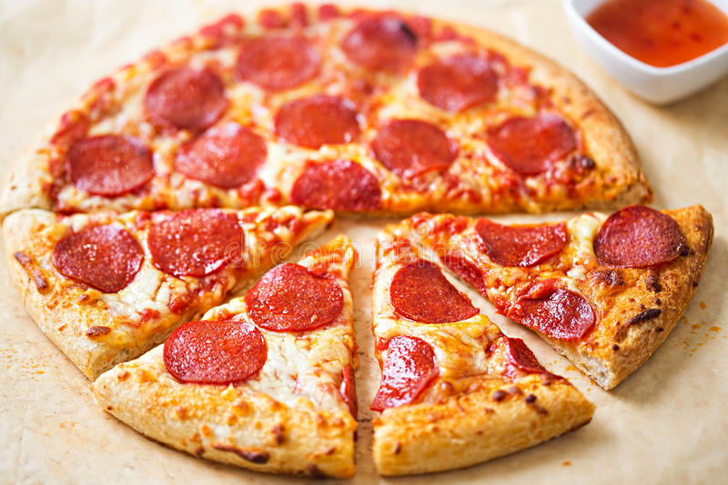 Pepperoni pizza with chilli dip royalty free stock image