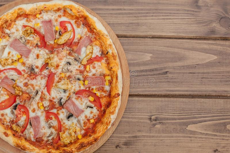 Pepperoni Pizza with Mozzarella cheese, Ham, Tomatoes, pepper, Spices . Italian pizza royalty free stock image