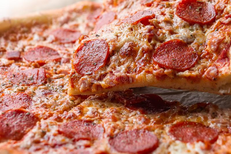 Pepperoni pizza with one slice cut off royalty free stock photo
