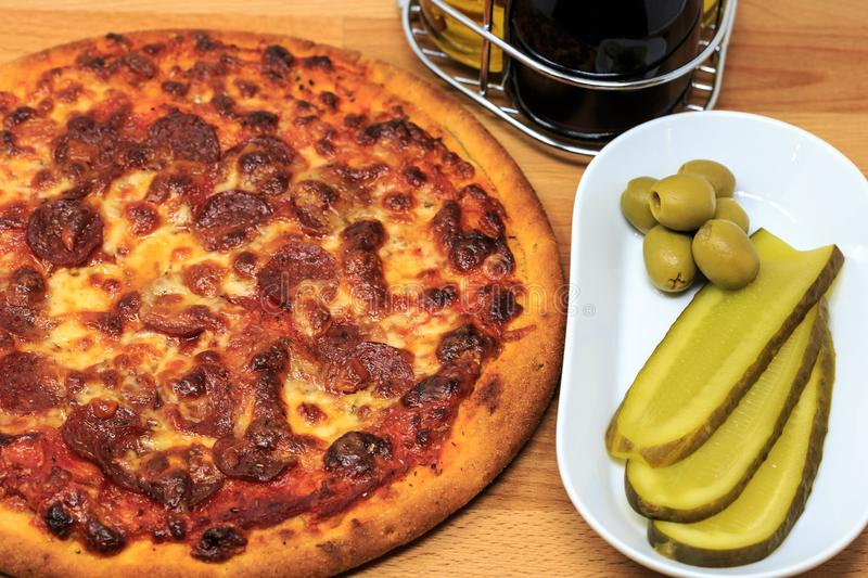 A pepperoni pizza with pickle and olives as a side stock image