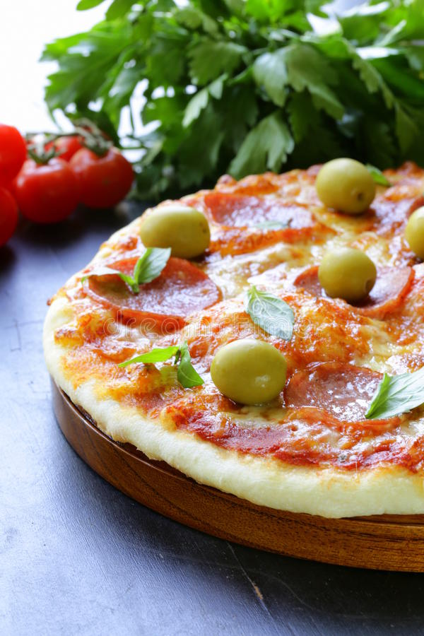 Pepperoni pizza with tomato sauce and herbs royalty free stock images