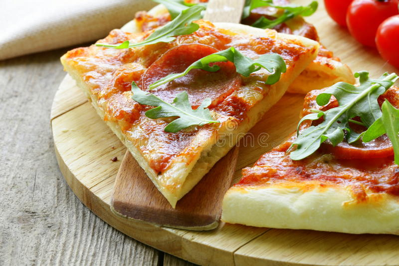 Pepperoni pizza with tomato sauce and herbs royalty free stock photos