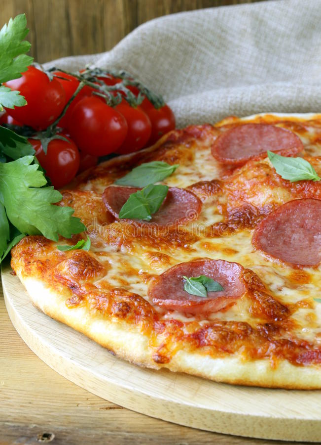 Pepperoni pizza with tomato sauce and herbs stock photo