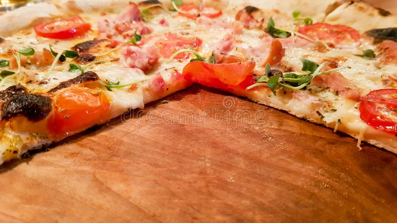 Pepperoni pizza on a wooden board with empty space, copy space. Pizza without three slices royalty free stock photos