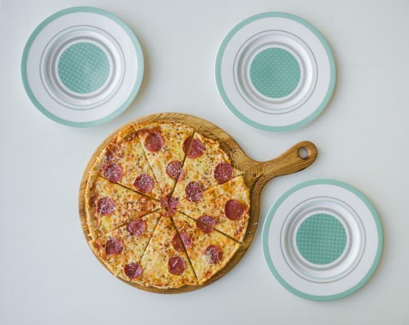 Pepperonipizza und drei leere Platten Vater, Mutter und Kinder, die eine große Pizza essen stockfotografie
