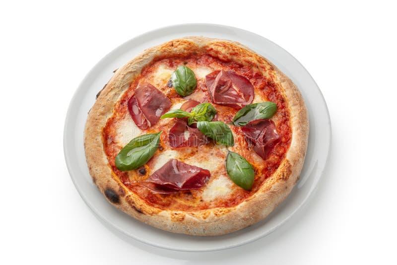 Pepperonispizza met spinazie en bacon op een witte plaat royalty-vrije stock afbeelding