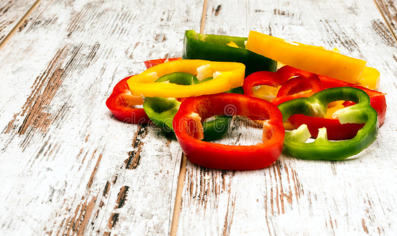 Peppers bell cut. Colored peppers bell cut on rustic background stock image