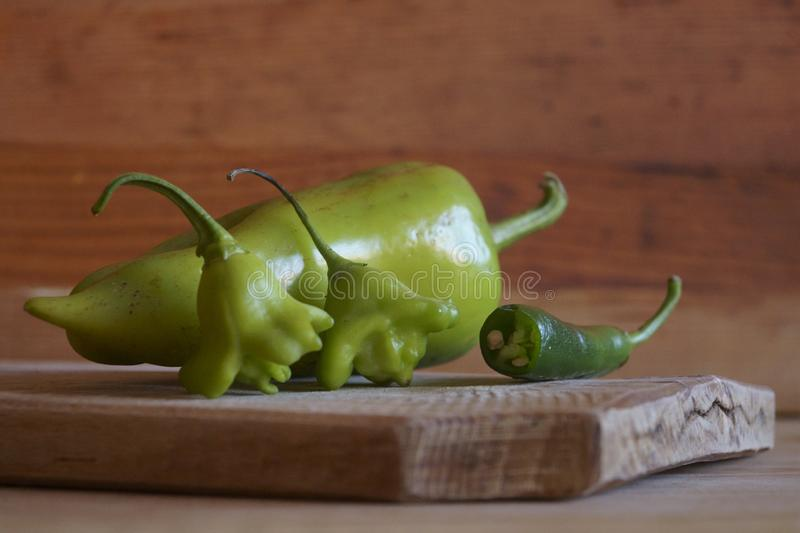 Green peppers on a wooden background - chili peppers and bell peppers royalty free stock photo