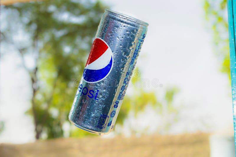 Pepsi può volo nell'aria con fondo vago fotografia stock