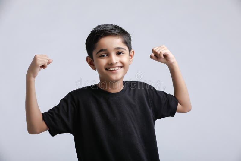 pequeña actitud india/asiática de la demostración del muchacho sobre el fondo blanco fotografía de archivo libre de regalías