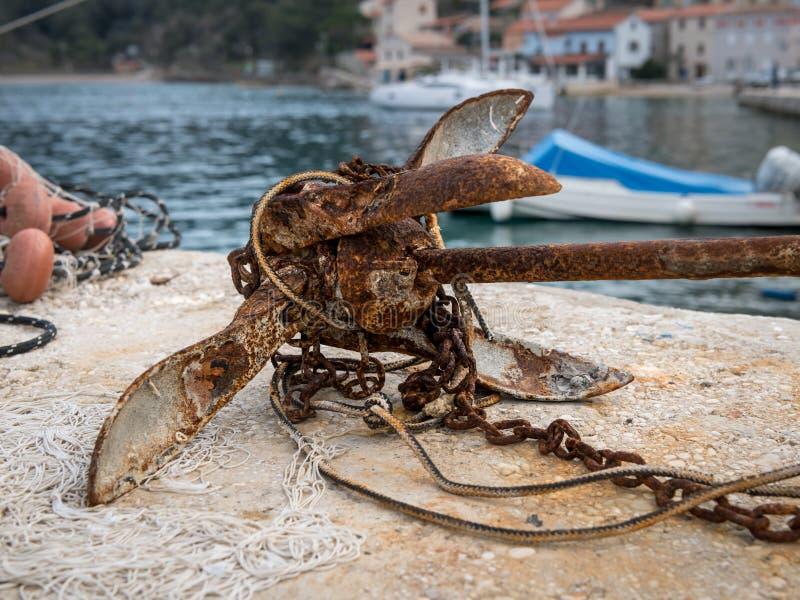 Pequeña ancla oxidada con la cadena que miente en la tierra foto de archivo