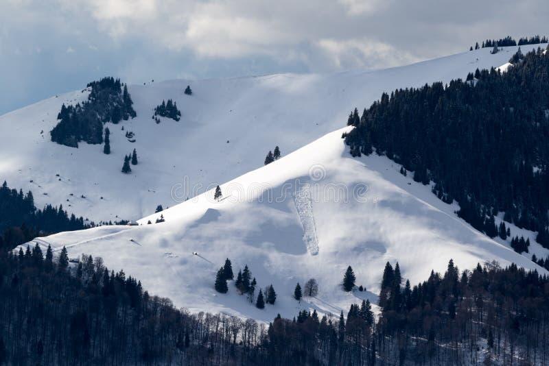 Pequeña avalancha que cae apagado un lado de una montaña imagen de archivo