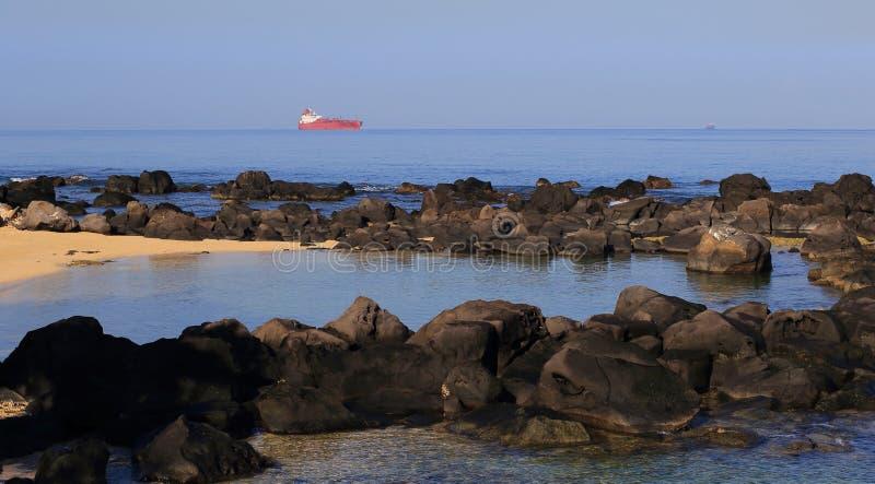 Pequeña bahía reservada con portacontenedores rojo en el horizonte fotos de archivo libres de regalías
