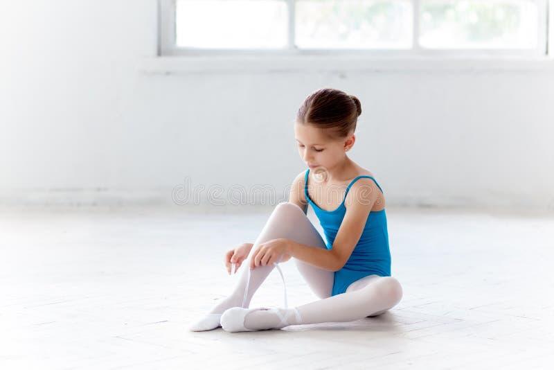 Pequeña bailarina hermosa en el vestido azul para bailar poniendo a pie los zapatos del pointe fotografía de archivo libre de regalías