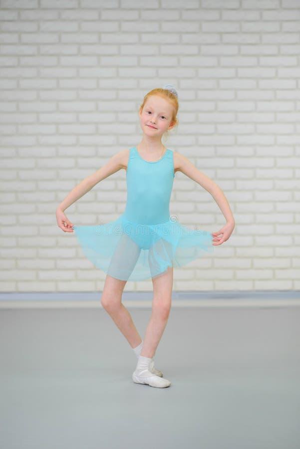 Pequeña bailarina linda en el baile azul del vestido en la clase del ballet imagen de archivo