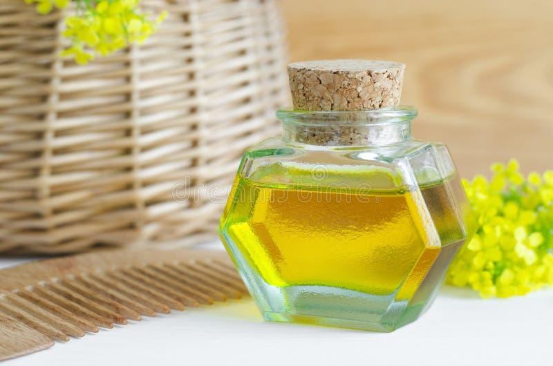 Pequeña botella de aceite cosmético natural y de peine de madera del pelo foto de archivo libre de regalías