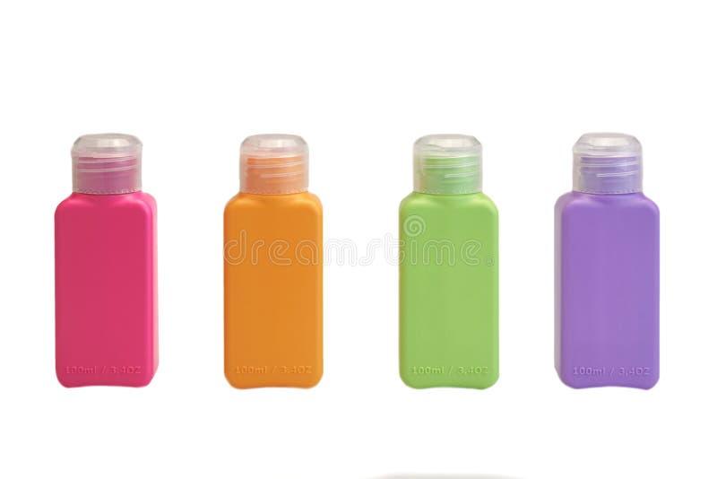 Pequeña botella plástica multicolora cuatro aislada en blanco fotografía de archivo libre de regalías