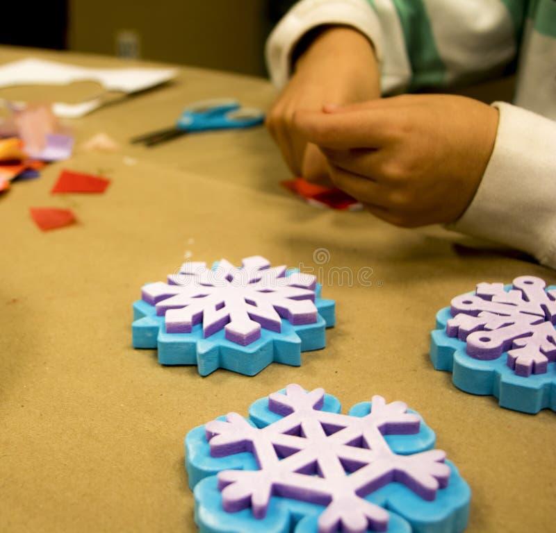Pequeña brocha verde con las matrices del copo de nieve y las manos de los childs imagen de archivo libre de regalías